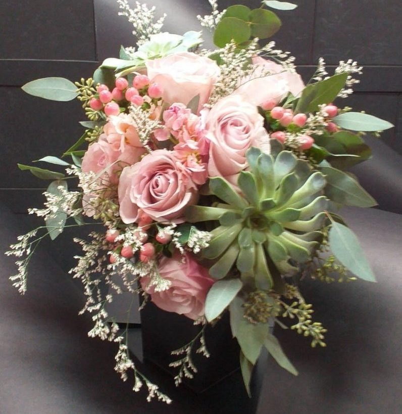 Light pink Roses, Succulents, and greenery Wedding Bouquet with a black background. Beautiful and stunning Wedding Bouquet.
